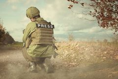 Journalist photographer in war conflict zone between shootings. Photographer in war conflict field zone observing Royalty Free Stock Images