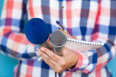 Journalist. Press conference. Media interview. Journalism. Female journalist at news conference, writing notes, holding microphones Royalty Free Stock Photos
