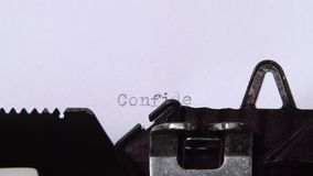 Journalist prints the word confidential on the retro typewriter. Close up. Journalist prints on the retro typewriter the word confidential, the title of a new stock video footage