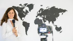 The journalist is reporting on the background of a large map of Royalty Free Stock Images