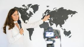 The journalist is reporting on the background of a large map of Royalty Free Stock Image
