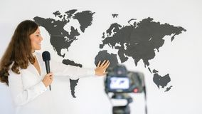 The journalist is reporting on the background of a large map of Stock Photo