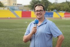 The journalist is reporting from the stadium Royalty Free Stock Photo