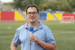 The journalist is reporting from the stadium. For television Royalty Free Stock Image