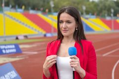 The journalist is reporting from the stadium. For television Stock Photos