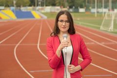 Journalist is reporting from the stadium for television Stock Photography