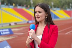 Journalist is reporting from the stadium for TV show Stock Images