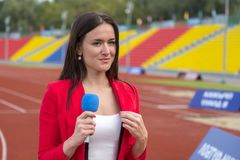 Journalist is reporting from the stadium for TV show Stock Photo
