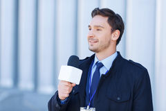 Journalist smiles while recording a newscast Royalty Free Stock Image