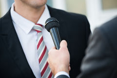 Journalist Taking Interview Of Businessman. Midsection of male journalist taking interview of businessman outdoors Royalty Free Stock Photography