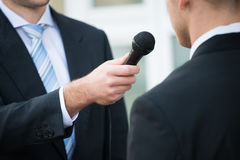Journalist Taking Interview Of Businessman. Midsection of male journalist taking interview of businessman outdoors Stock Images