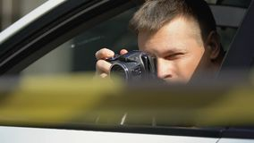 Journalist taking photo over barricade tape hiding in car, crime investigation. Stock footage stock video