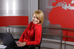 Journalist and television manager. Profile of attractive journalist and presenter in front of the laptop looking at the camera in a television studio Stock Images