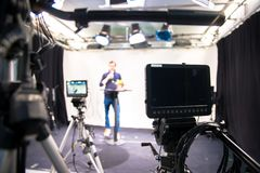 Journalist in a television studio is talking into a microphone, blurry film cameras. Male journalist in a television studio talks into a microphone, film cameras royalty free stock photography