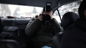 A journalist traveling in a taxi with a camera in hand and check the flash operation stock video footage