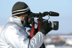 Journalist with a videocamera. The journalist with a videocamera in the winter morning Stock Image