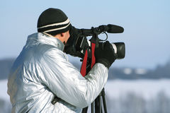The journalist with a videocamera. In the winter morning Royalty Free Stock Image