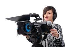 Journalista bonito da jovem mulher com microfone e câmera no estúdio da televisão no branco foto de stock