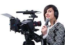 Journalista bonito da jovem mulher com o microfone no est?dio da televis?o no branco imagem de stock