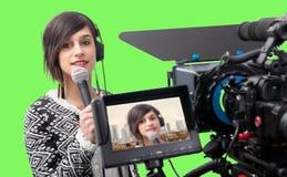 Journalista bonito da jovem mulher que apresenta o relatório no estúdio da televisão foto de stock