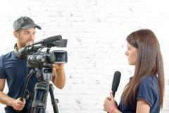 Journalista da jovem mulher com um microfone e um operador cinematográfico Fotos de Stock Royalty Free