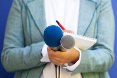 Journalista fêmea na conferência de imprensa, escrevendo as notas, guardando o microfone fotografia de stock