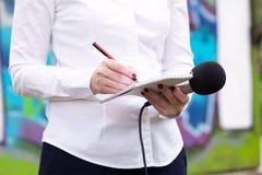 Journalista fêmea na conferência de imprensa, escrevendo as notas, guardando o microfone imagens de stock