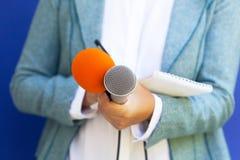 Journalista fêmea na conferência de imprensa, microfone da terra arrendada, escrevendo notas fotos de stock
