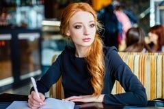 Journalista fêmea novo talentoso que trabalha em seu novo livro fotos de stock
