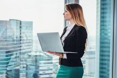 Journalista fêmea que escreve um artigo usando estar de pensamento do portátil na janela e a vista do distrito financeiro da cida imagem de stock