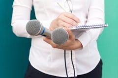 Journalista fêmea que toma notas na conferência de imprensa fotos de stock