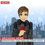 Journalista fêmea que trabalha no inverno na frente da cidade com os arranha-céus que guardam o microfone Foto de Stock Royalty Free