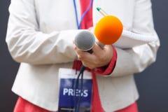 Journalista na conferência de imprensa, escrevendo as notas, guardando o microfone fotos de stock