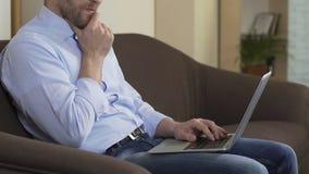 Journalista que senta-se no sofá com portátil e que pensa no artigo novo, ocupação filme