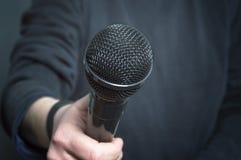 Journalistdanandeanförande med mikrofonen och handen som gör en gest begreppet för intervju Fotografering för Bildbyråer