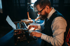 Journaliste barbu en verres dactylographiant sur la machine à écrire Images libres de droits