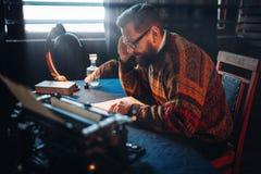 Journaliste barbu en verres lisant le sien travail Photo stock