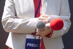 Journaliste féminin à la conférence de presse, écrivant des notes, tenant le microphone photo stock