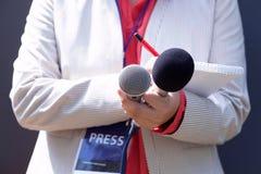 Journaliste féminin à la conférence de presse, écrivant des notes, tenant le microphone image libre de droits
