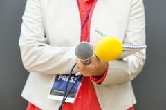 Journaliste féminin à la conférence de presse, écrivant des notes, tenant le microphone images stock