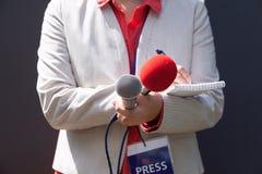 Journaliste féminin à la conférence de presse, écrivant des notes, tenant le microphone photo libre de droits