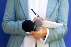 Journaliste féminin à la conférence de presse, écrivant des notes, tenant le microphone photographie stock libre de droits