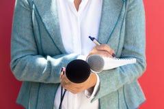 Journaliste féminin à la conférence de presse, écrivant des notes, tenant le microphone image stock