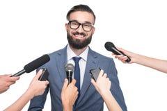 journalisten die met microfoons glimlachende knappe zakenman interviewen, Stock Afbeeldingen