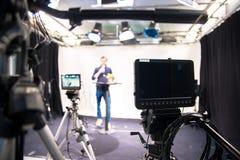 Journalisten i en televisionstudio talar in i en mikrofon, oskarpa filmkameror royaltyfri fotografi