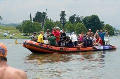 Journalister och massmedia fotograferar och filmar den Midmar milen från ett uppblåsbart fartyg med simmare i förgrund. Royaltyfri Bild