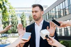 journalister som intervjuar den allvarliga affärsmannen med mikrofoner Royaltyfria Foton