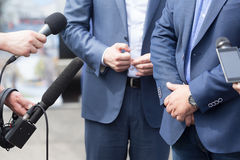Journalists holding microphones conducting media interview. News conference. Reporters making interview with businessman, politician or spokesman. Press Royalty Free Stock Photos