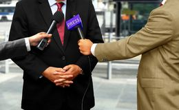 Journalists with microphones interviewing corporate spokesperson. Journalists interviewing corporate spokesperson with microphones Stock Photography