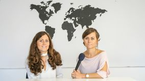 Journalists in studio. Two women in studio with microphone and world map on white background Royalty Free Stock Photos